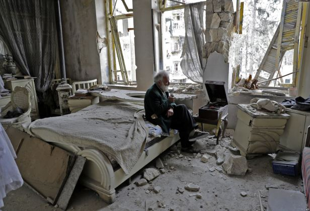 Sedamdesetogodišnjak puši lulu i sluša muziku na gramofonu u spavaćoj sobi svog devastiranog doma, Alep, 9. mart 2017. Foto Joseph Eid AFP